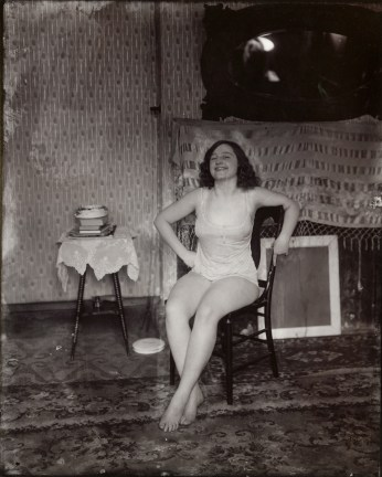 Black-and-white photograph of a woman smiling sitting in a chair