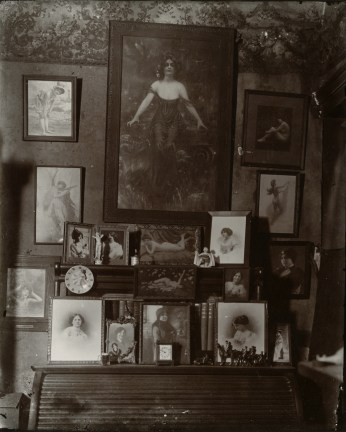 Black-and-white photograph of a desktop and wall with assorted photographs and paintings of women
