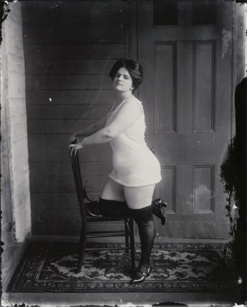 Black-and-white photograph of a woman posing with her knee on a chair