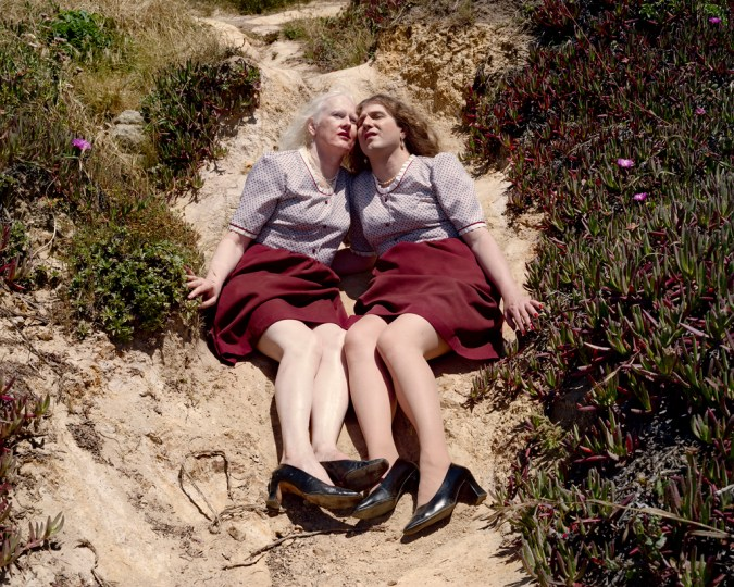 Color photograph of women in matching outfits of lilac tops, red skirts, and black high heels seated cheek-to-cheek on a hillside