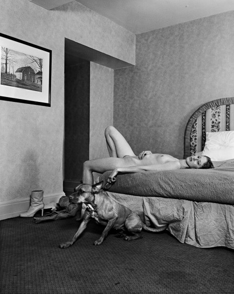 Black-and-white photograph of a nude woman lying on a bed with a dog seated on the floor beside her