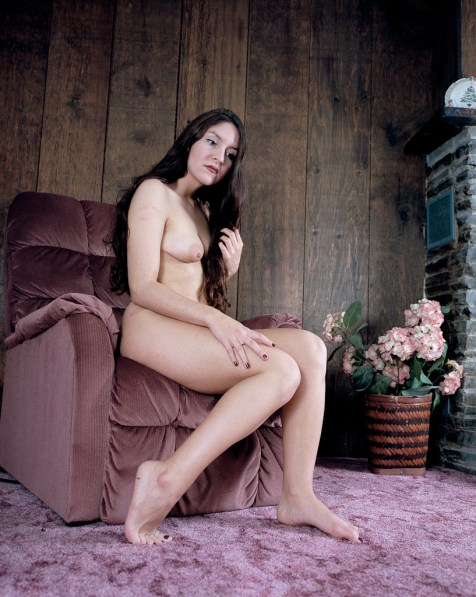 Color photograph of a nude woman seated on the edge of an armchair in a wood paneled room