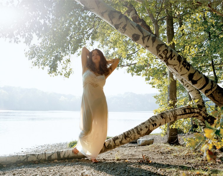Color photograph of a woman in a long white dress standing on a fallen tree trunk on the shore of a still lake