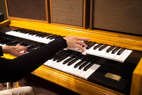 a close up of hands playing the organ