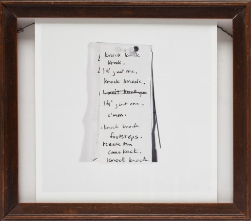 A framed photograph of a note with cursive writing describing someone knocking