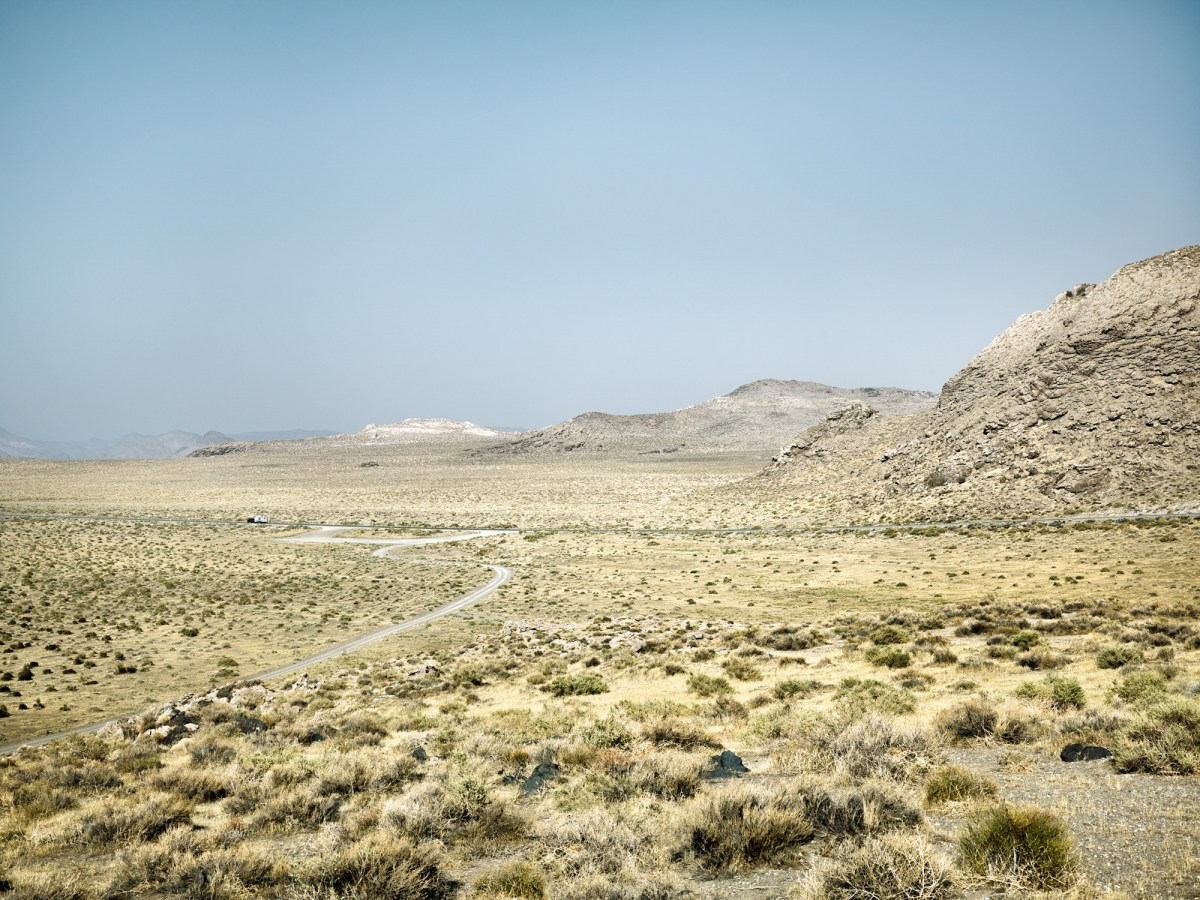 Color photograph of a desert landscape with a road curving through a valley with low rocky hills