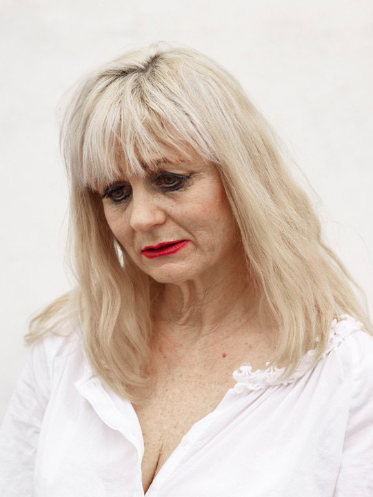 Color photographic portrait of a woman with platinum blonde hair, red lipstick, and a downcast gaze against a blank white wall