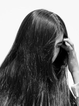 Black-and-white photographic portrait of a woman with her face obscured by long dark hair