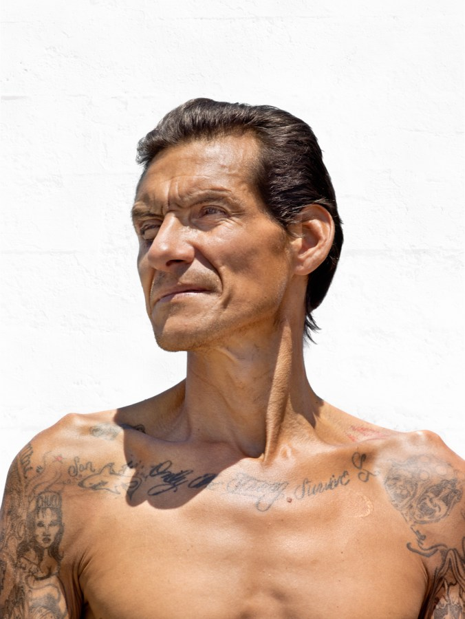 Color photographic portrait of a shirtless man with tattoos across his collarbone against a blank white wall
