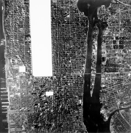 Black-and-white aerial photograph of a segment of Manhattan, New York, with Central Park and two smaller rectangles in midtown blocked out in white