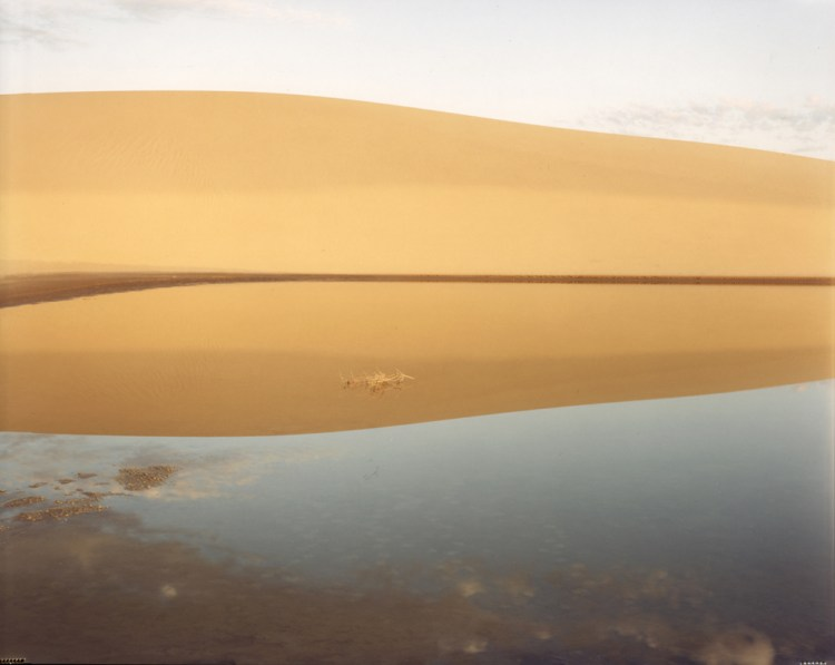 Color photograph of a sand dune reflected in a still body of water