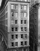 Black-and-white frontal photograph of an eight-story building receding into the distance
