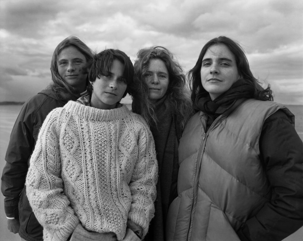 Black-and-white photographic portrait of four young women dressed in sweaters standing under a cloudy sky
