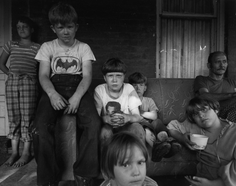 Black-and-white photograph of six children and a man seated around a couch on a porch