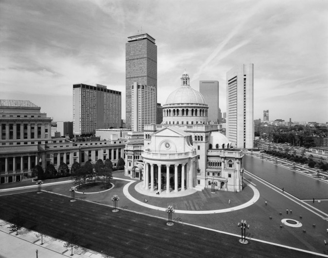 Black-and-white photograph of a Greco-Roman style building with a domed roof amid modern city high rise buildings