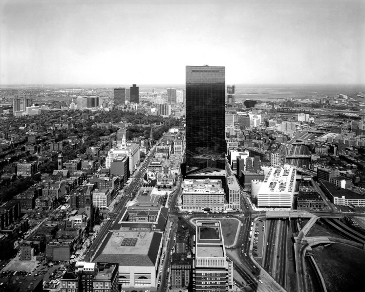 Black-and-white photograph of a rectangular glass high-rise building rising above surrounding city buildings