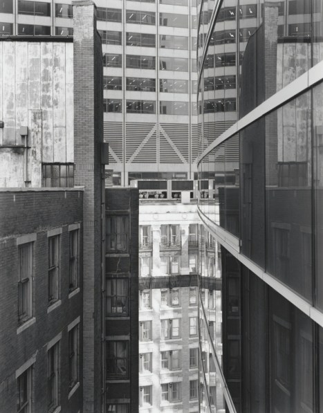 Black-and-white photograph of a modern high-rise building between other city buildings