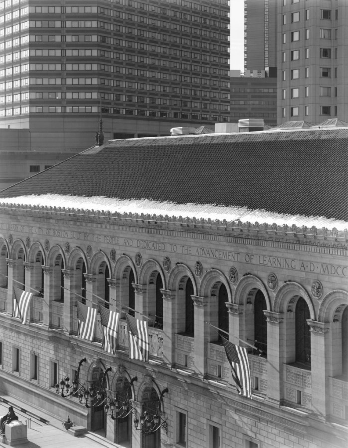 Black-and-white photograph of a low stone building flying American flags on its façade in front of modern high-rise buildings