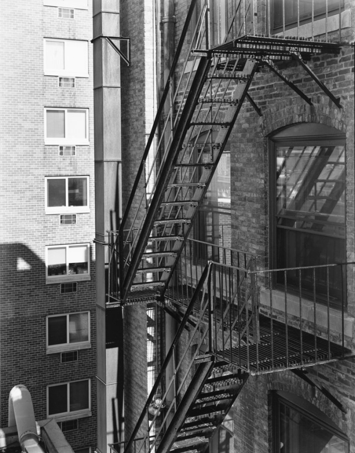 Black-and-white photograph of fire escapes on the shadowed side of a brick building