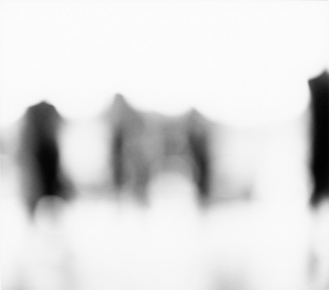 Black-and-white out-of-focus photograph of figures against a white background
