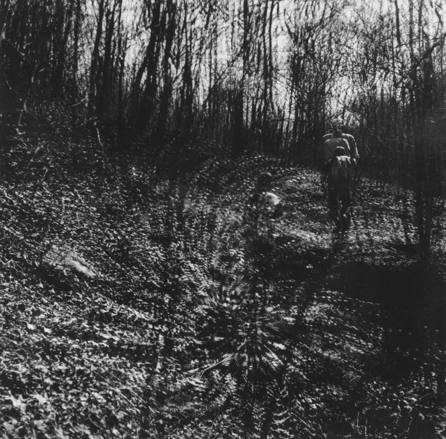 Black-and-white multiple-exposure photograph of two figures standing amid bare trees