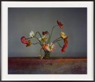 Color photograph of multi-colored flowers in glass vase
