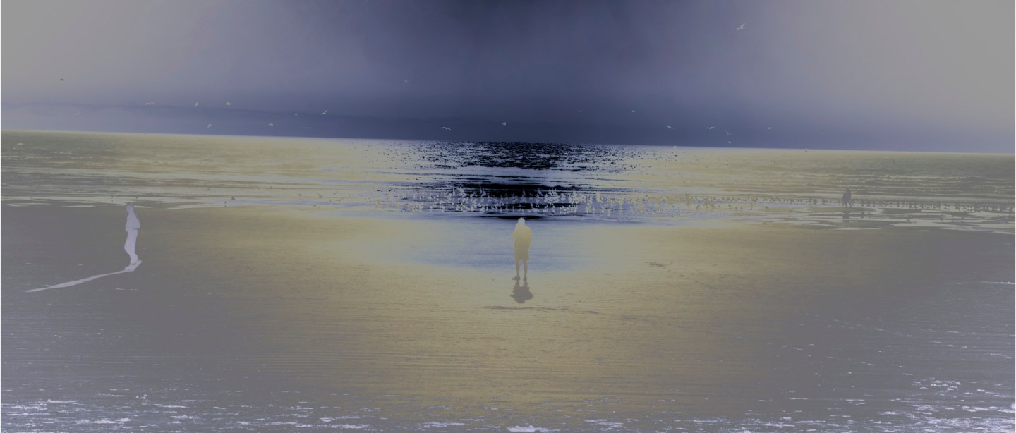 Inverted color photograph of a person standing on the seashore looking at the horizon