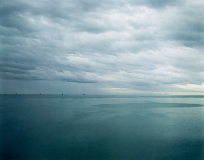 Color photograph of five black structures on the horizon rising above the waters of a calm sea