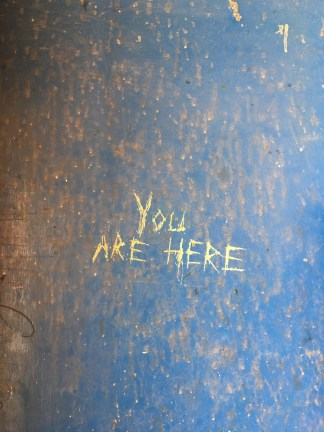 Color photograph of the words YOU ARE HERE scratched onto a painted blue rusty metal surface