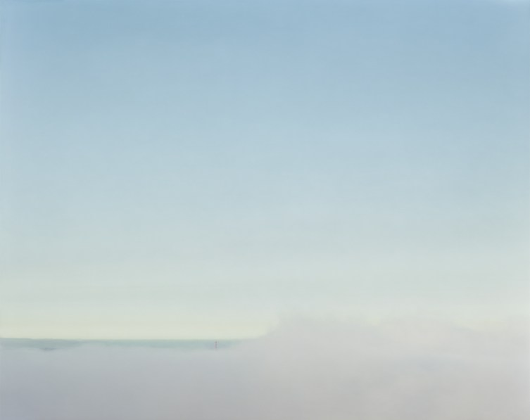 Color photograph of the Golden Gate Bridge on the horizon almost completely obscured by low-lying fog under a clear pale blue sky