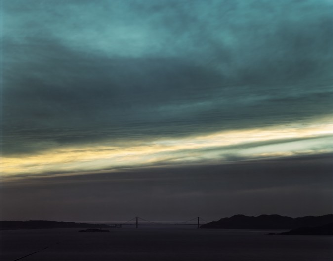 Color photograph of the distant Golden Gate Bridge under a linear break in the clouds