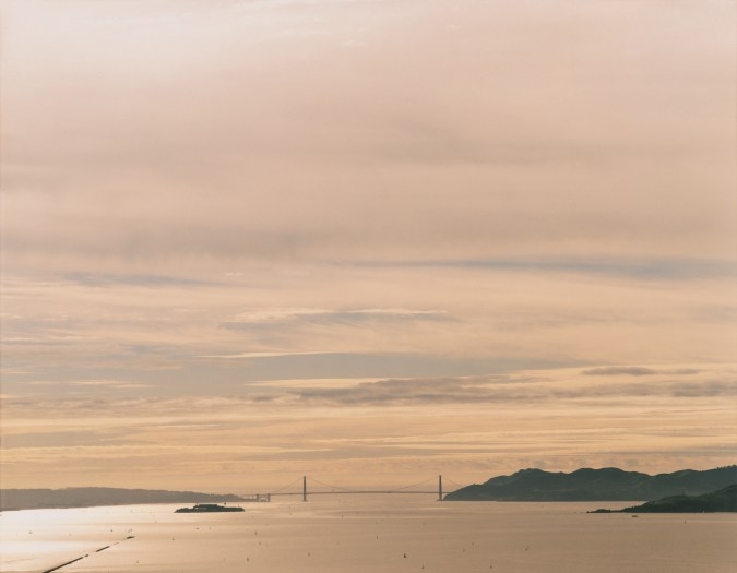 Color photograph of the distant Golden Gate Bridge under a clouded pastel pink and orange sky