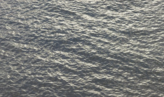 Color photograph of small waves on the surface of the sea