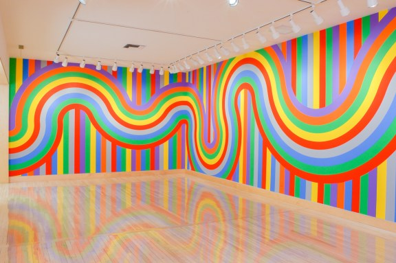 Installation view of a set of wiggly lines in colors of the rainbow running across two walls painted with vertical rainbow stripes