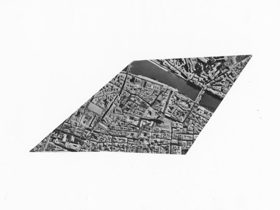 Rhombus-shaped black-and-white photograph of an aerial view of a river running through a city