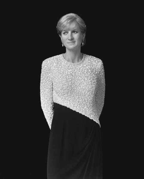 Black-and-white frontal portrait of a wax figure of a woman in an asymmetrically patterned dress with her hands behind her back