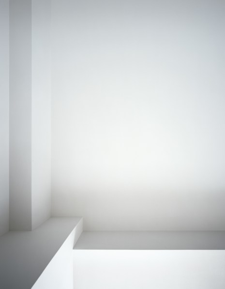 Photograph of a white ceiling with linear beams next to a window cut-out in varying shades of gray