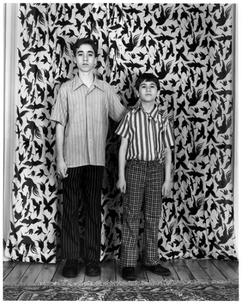 Black-and-white photograph of two boys in striped shirts standing in front of a curtain with a bird pattern