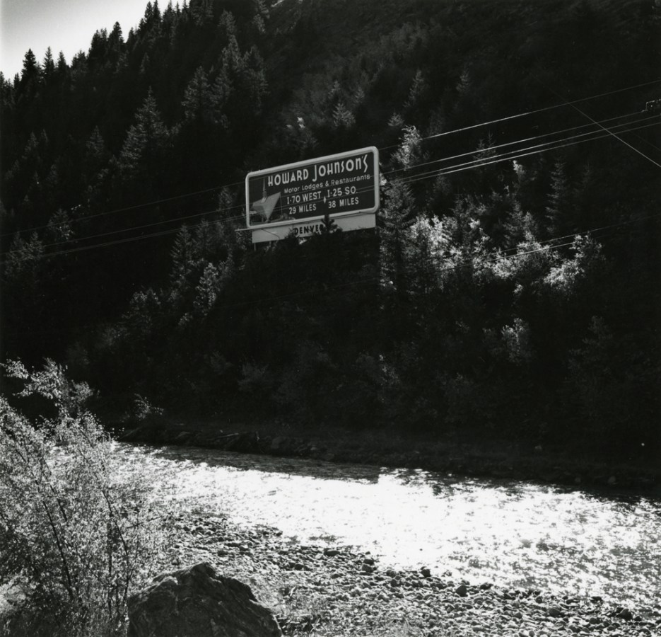 A black and white photograph of a billboard advertising Howard Johnson's against pine trees and a river in the foreground.