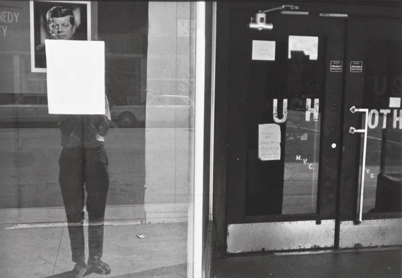 A black and white photograph of a self portrait of the artist reflected in a shop window