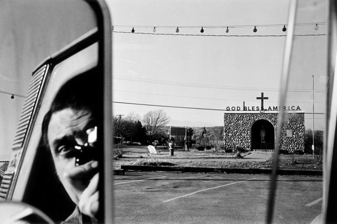 A black and white photograph of a self portrait of the artist reflected in the side mirror of a car with a church in the right of the frame