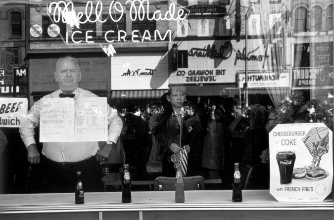 Black-and-white photograph of a man looking out the window of an ice cream parlour