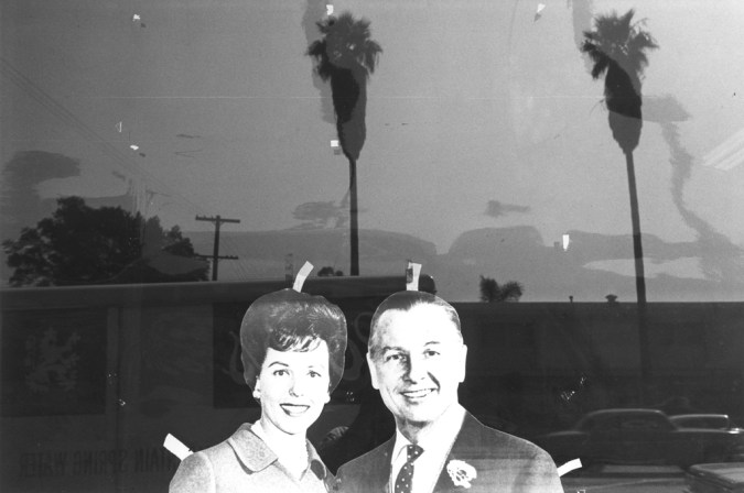 Black-and-white photograph of cut outs of a man and woman taped in a window with palm trees in the reflection