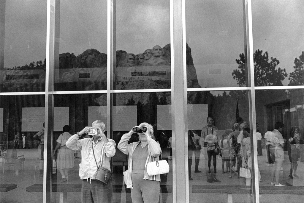 Black-and-white photograph of a man and woman looking out of the frame with binoculars with reflections in the glass wall behind them