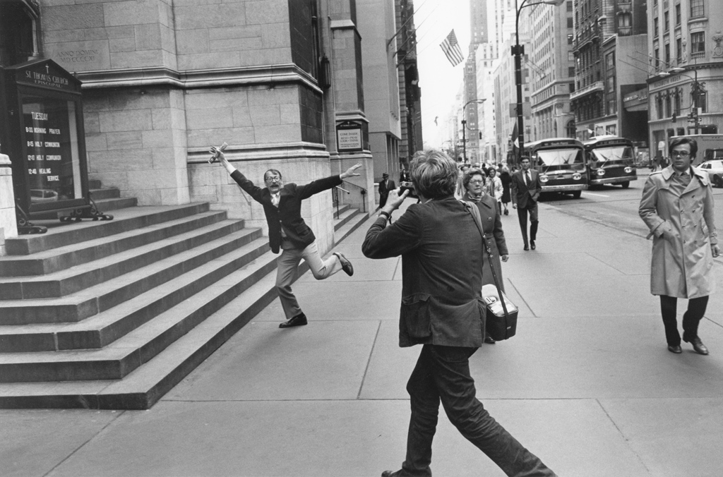 Black-and-white photograph of a man taking a photograph of a man doing a jumping motion on a city sidewalk