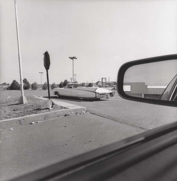 Black and white photograph out the window of a car of a 1950s convertible parked in an empty parking lot
