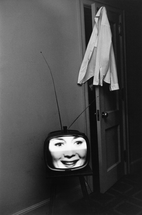 Black-and-white photograph of a television with a laughing face on screen and a shirt hanging from an open door