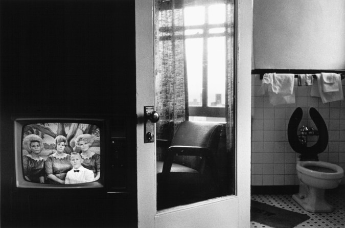Black-and-white photograph of a television with figures on screen, a reflection in a door mirror, and a toilet