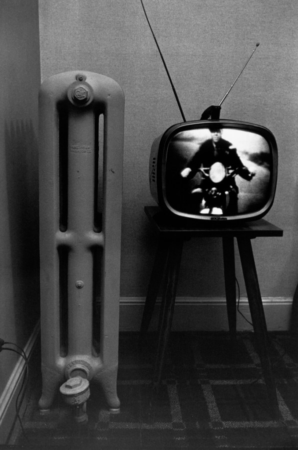 Black-and-white photograph of a television with a motorcyclist on screen and a radiator