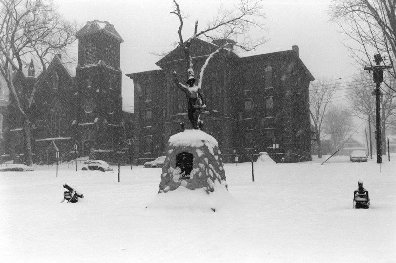 Black and white photograph of a monument covered in snow